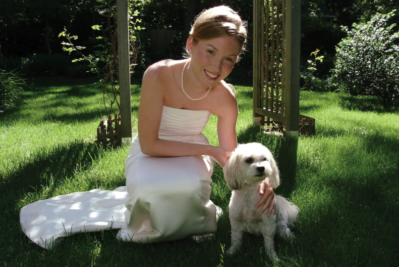 A bride poses with her well-behaved pooch