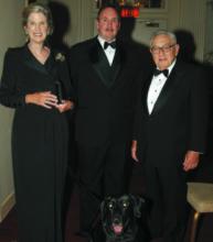 Nancy Kissinger, Detective Raymond Clair with Winston, and Dr. Henry Kissinger.