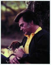Conrad Twitty deep in thought holding a hound.