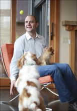 Rover.com CEO, Aaron Easterly, holds his dog Caramel as he plays with the dog he is sitting, Charlie.