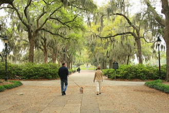 A couple walking their dog through one of Savannah's many squares.
