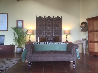 Ginger House luxuriously-appointed furnishings an antique carved headboard, fine art, a fireplace, kitchenette, overhead fan, loveseat and a glorious 180-degree panoramic view of Lake Atitlan.